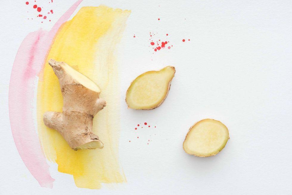 Ginger next sliced ginger on a white table