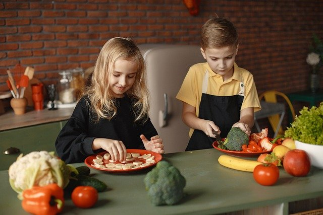This shows young children preparing food at school or nursery