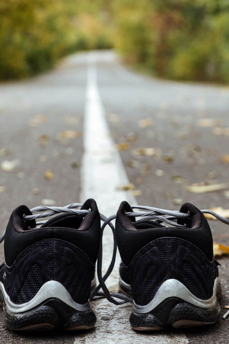 black running shoes on a street before a run