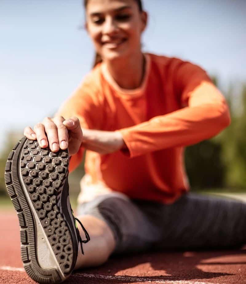 girl wearing orange shirt stretching on a track