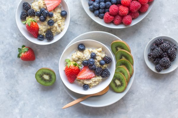How much sugar should I have a day, kiwi and berries with oatmeal in white bowls