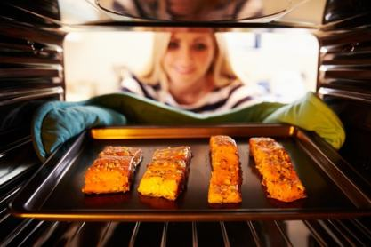 Putting salmon fillets in oven