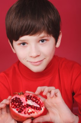 Boy with half of a pomegranate