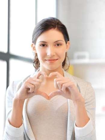 Happy woman making heart gesture