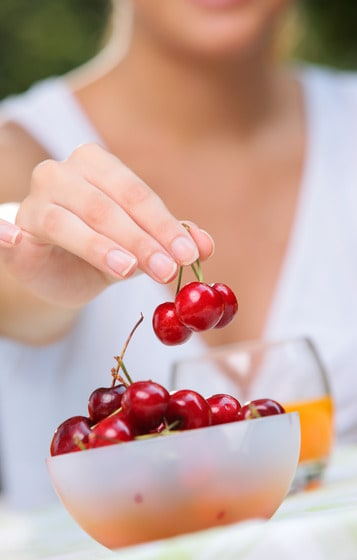 Woman grabbing cherries