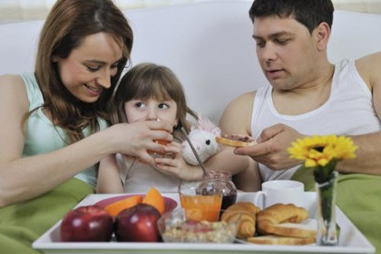 Family eating breakfast in bed