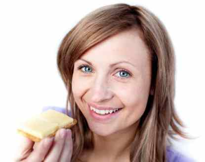 Woman eating cheese on a cracker