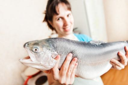 Woman holding raw fish, smiling