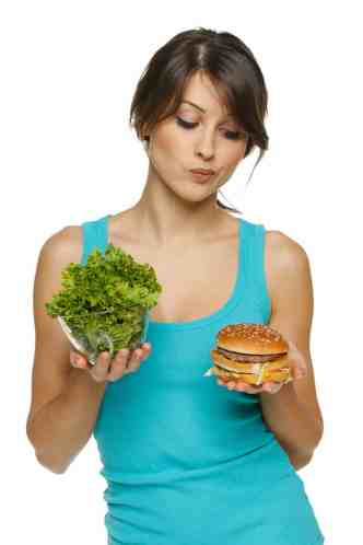 Woman deciding between a burger and lettuce