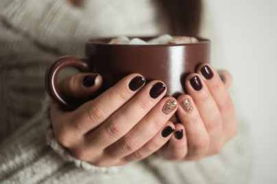 Brown cup with cocoa and marshmallow in the hands of the girl