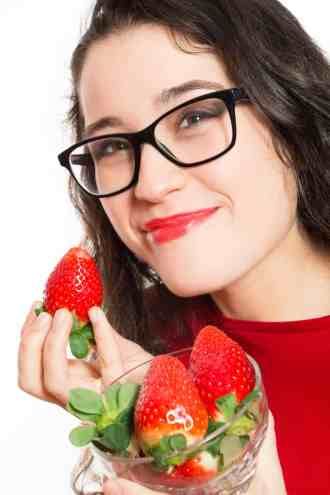 Funny woman with eyeglasses eating strawberries