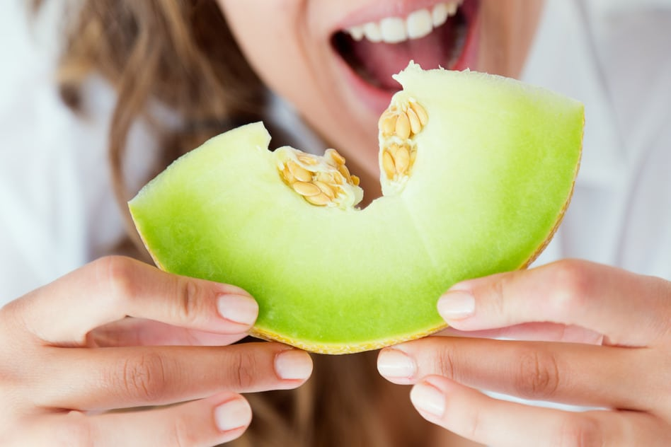 Young woman eating honeydew