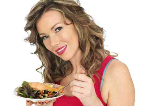 Young Woman Eating Salmon with Mixed Bean Salad