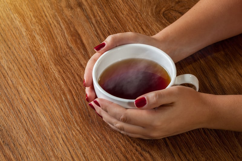 Woman holding a mug of hot tea