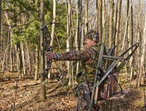 bow hunter in camouflage pulling back a compound bow in the forest