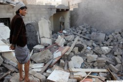 A Yemeni man stands at his house destroyed by Saudi airstrikes near Sanaa Airport, Yemen, Tuesday, March 31, 2015. (AP Photo/Hani Mohammed)
