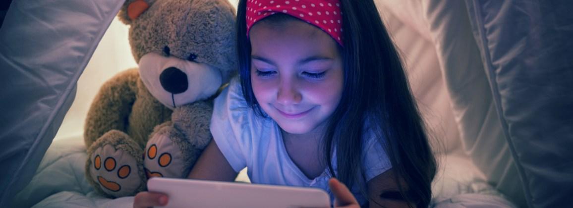 Little girl using digital tablet in bed
