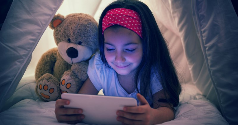 Little girl using digital tablet in bed