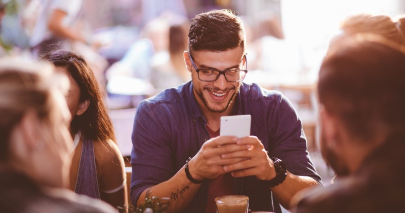 Happy man at coffee shop texting on mobile phone