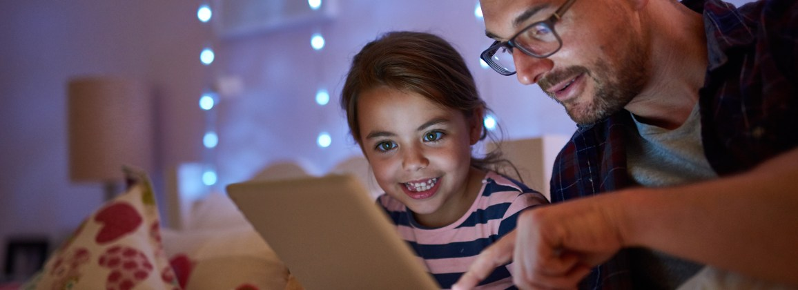 Shot of a little girl and her father using a tablet before bedtime