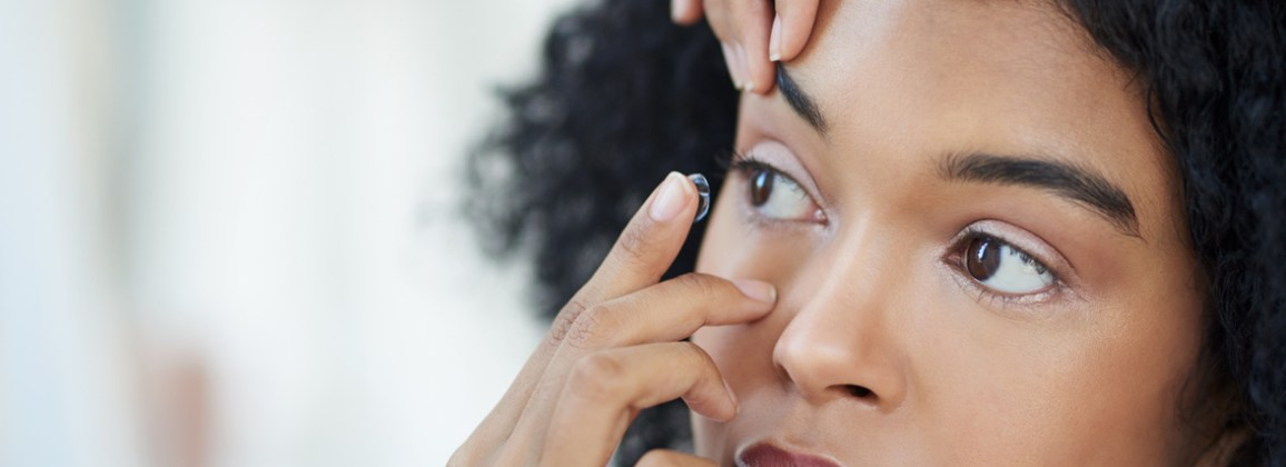 Woman putting contact lens in eye