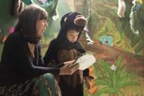 Student reading their rainforest animal presentation with their teacher