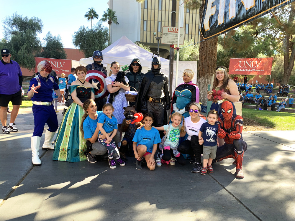 Children posing for a photo with people dressed as super heroes and Disney characters