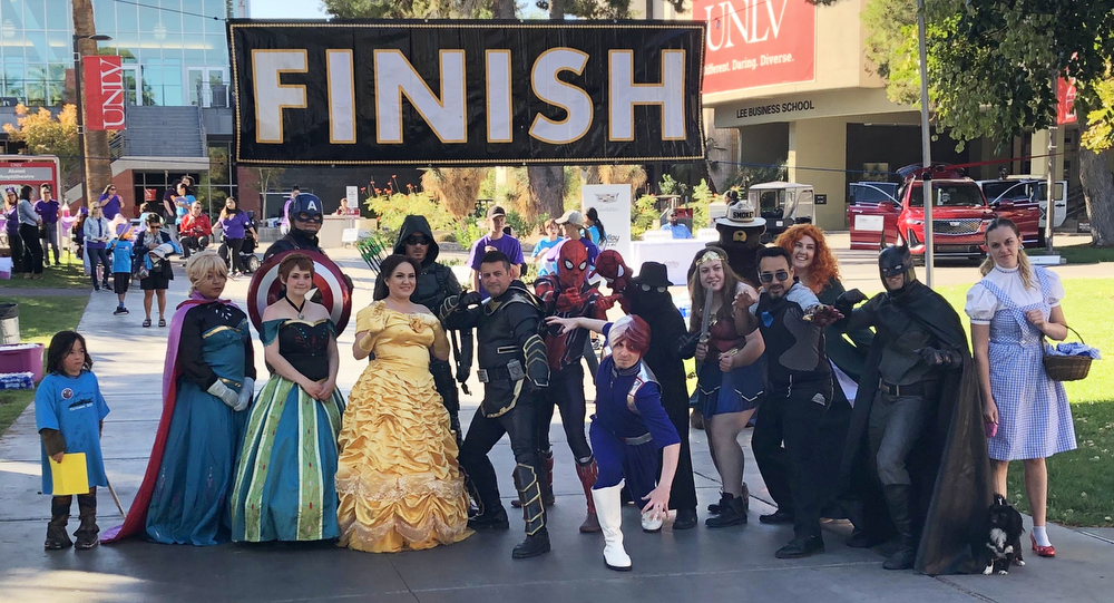 A group of people dressed as super heroes and Disney characters at the finish line
