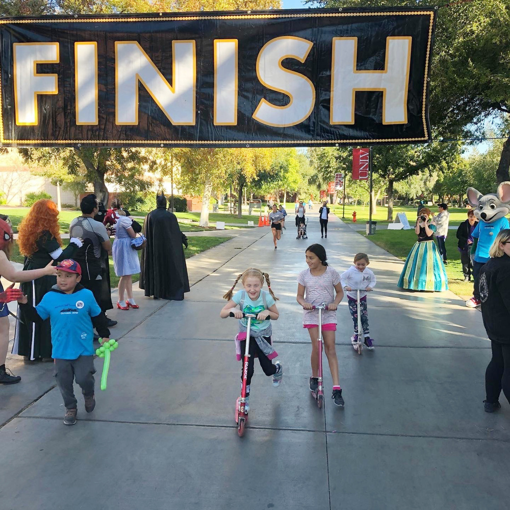 Children crossing the finish line on scooters