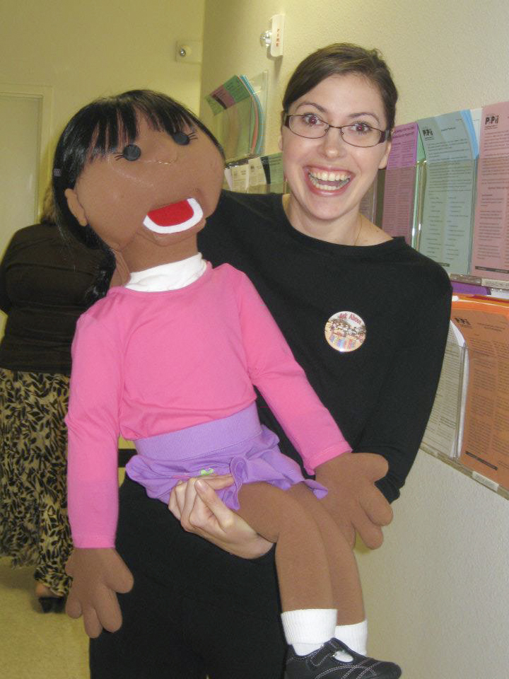 A smiling woman holding one of the Include Me puppets