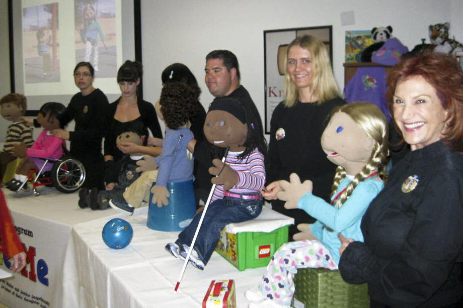 A group of people posing with the Include Me puppets