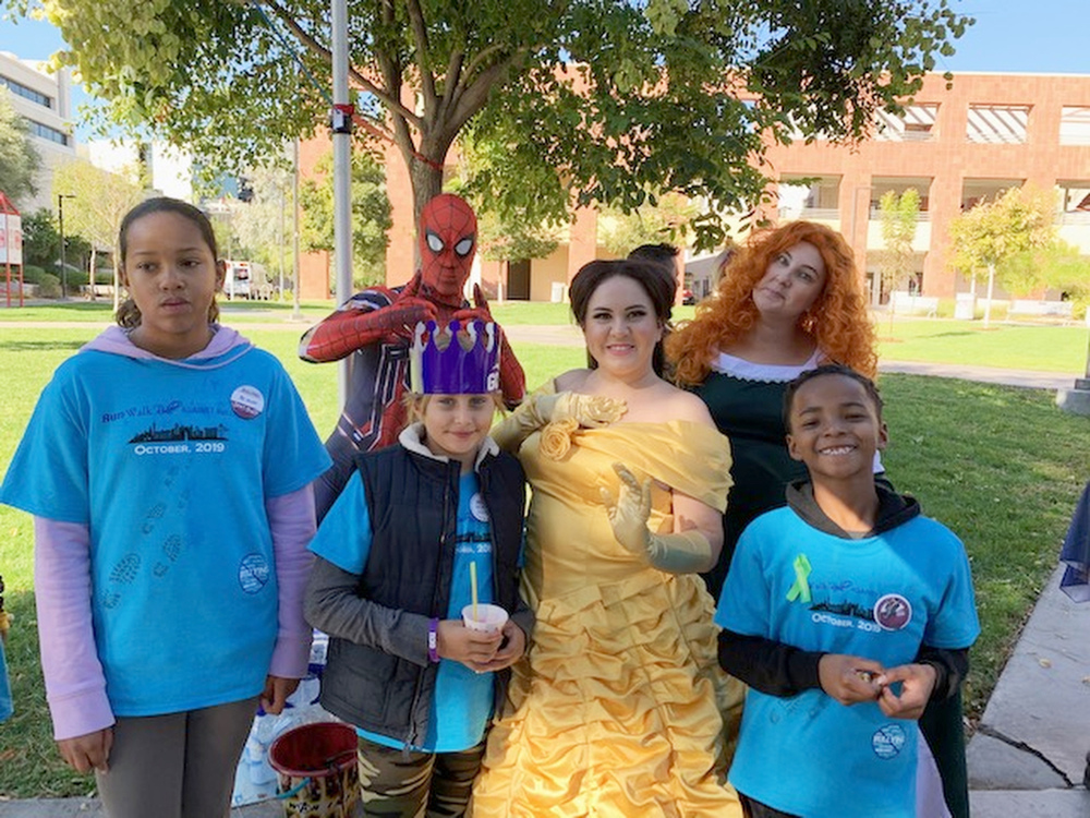 Children posing for a photo with people dressed like super heroes and