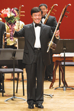 Warren Chang holds his er-hu, a classical Chinese instrument, after a performance.