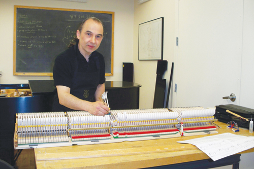 Yuri Melekh intimately knows the inner-workings of a piano. Here, he is fixing some hammers.
