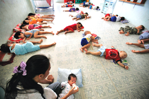 In this photo taken on Oct. 12, children who are HIV positive, are orphans, or live with their HIV positive mothers at the Mai Tam Center in Ho Chi Minh City rest on the floor of the center. (Photo by David Guttenfelder/AP)