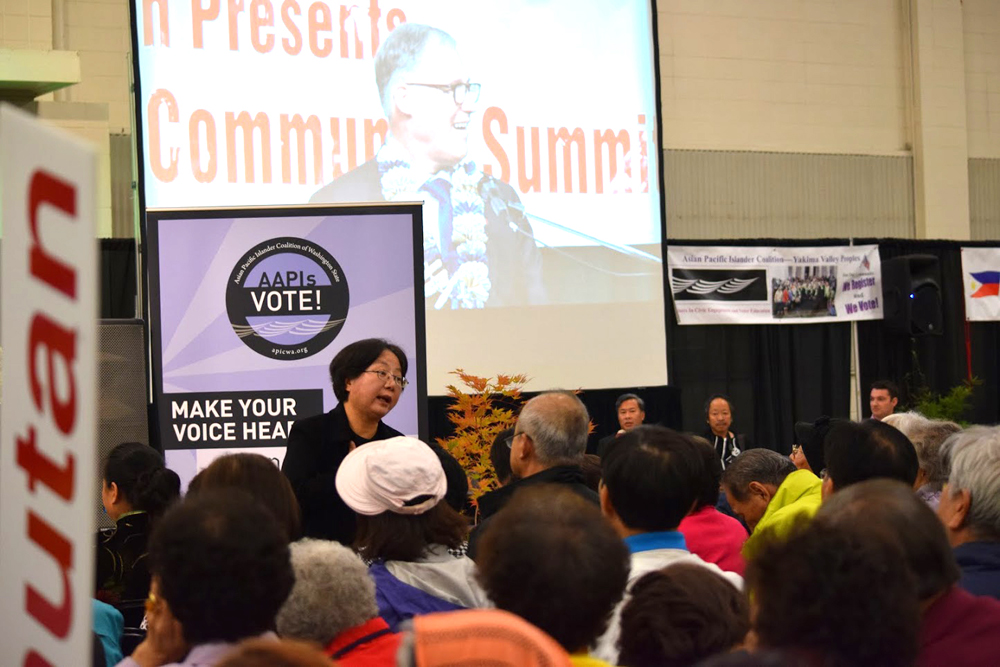 A translator interprets in Korean during the governor candidate forum. (Photo by Arlene Dennistoun/NWAW)