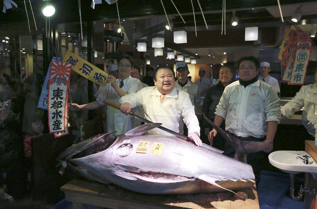 Kiyoshi Kimura, center, president of Kiyomura Co., poses with the bluefin tuna that he won in Tokyo on Jan. 5, 2017. (AP Photo/Eugene Hoshiko)