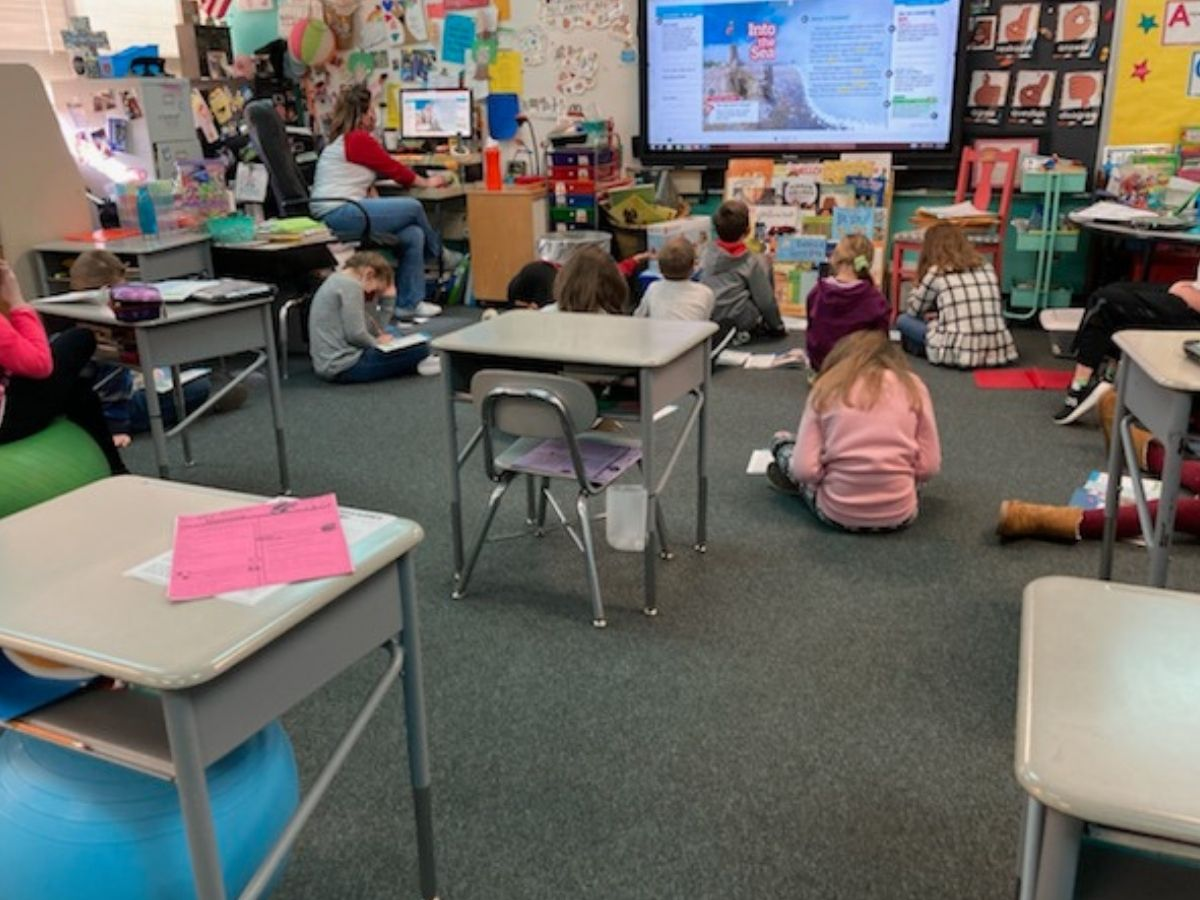 students watching board as teacher shows book