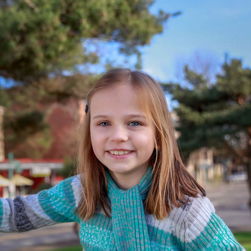 Image of young child with prosthetic eye outdoors, wearing a blue striped sweater
