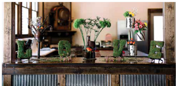 """Topiary letters spell """"LOVE"""" on a table."""