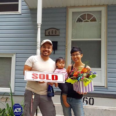 "a family stands in front of their new home with a ""sold"" sign"