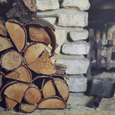 Firewood stacked next to a fireplace.