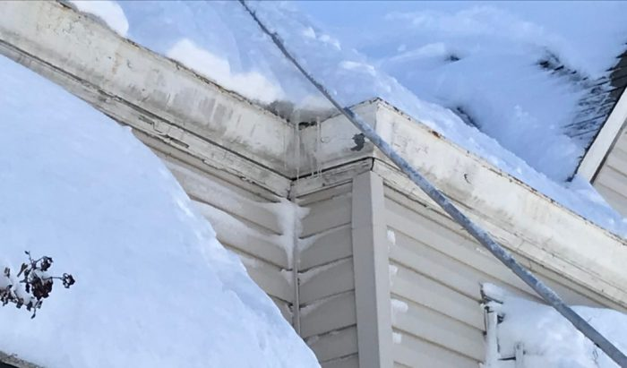You can see an ice dam forming above these icicles in the roof valley. The gutter has already filled with refrozen meltwater.