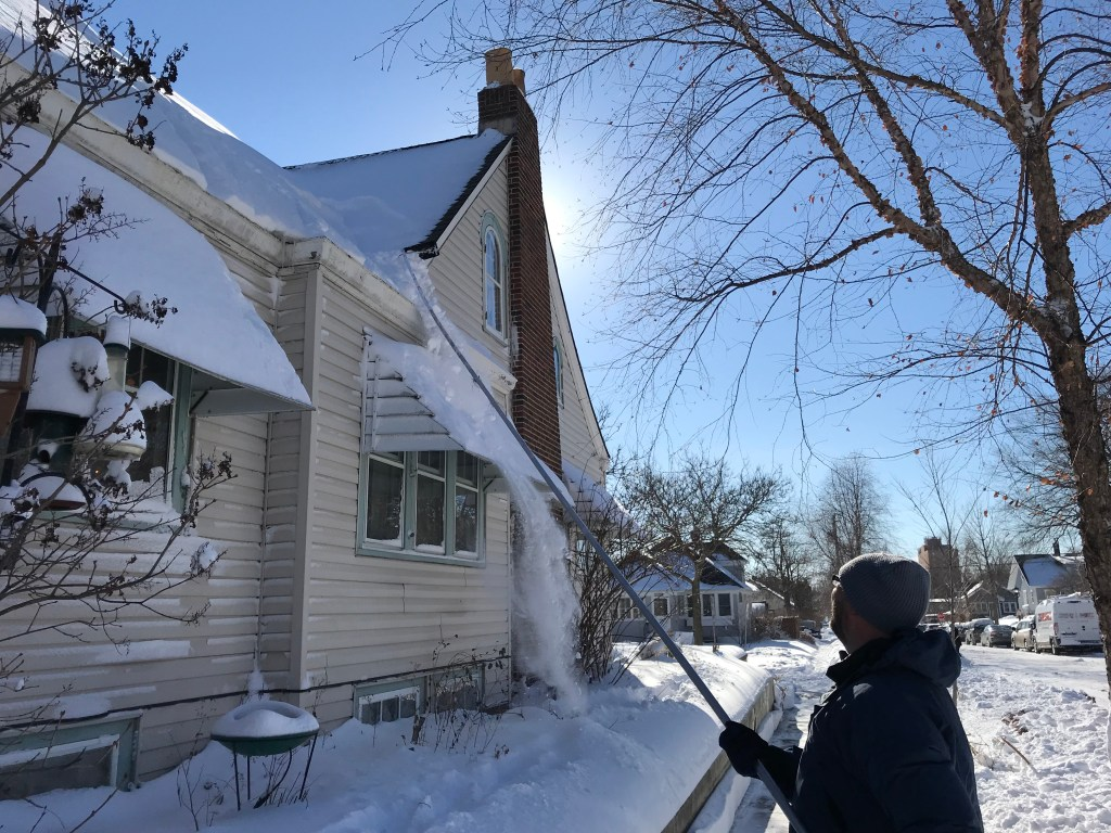 a roof rake removes snow from a roof valley