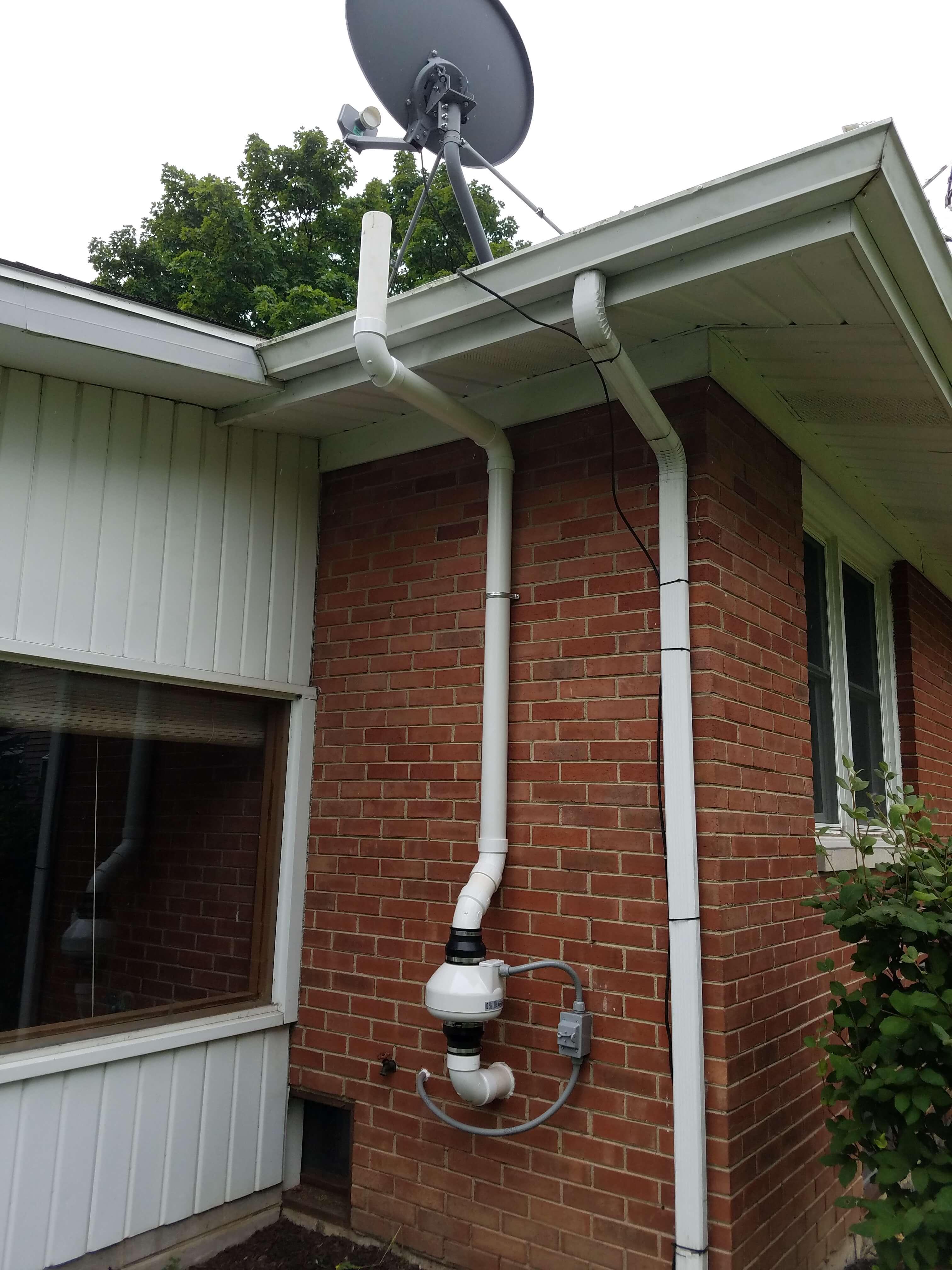 radon mitigation system along brick wall outside