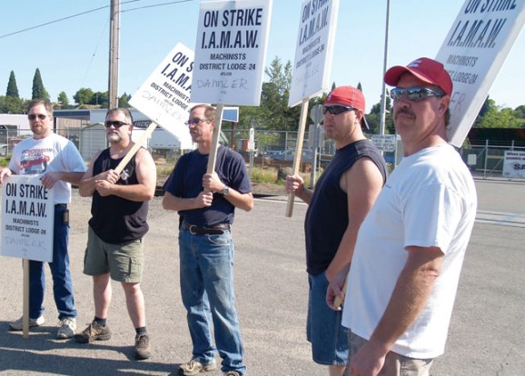Day one on strike at Daimler: Machinists Local 1005 members Todd Barnes, Jeff Bowes, Mike Brandt, Mike Coelho, and Terry Weese picket outside a plant gate six to noon July 1.