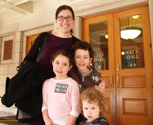 Sick pay advocate Andrea Paluso of Family Forward Oregon, pictured above with her children outside Portland City Hall, put together a union-community coalition that won an ordinance extending earned sick days to a quarter of a million Portland workers who didn't have it.