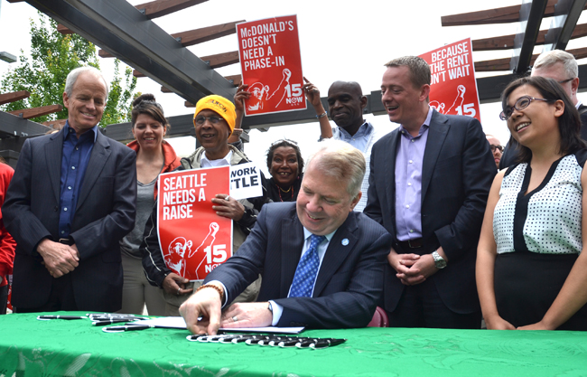 """Minimum wage campaigners celebrate as Seattle Mayor Ed Murray signs an ordinance creating a $15-an-hour city minimum wage. """"The economic policy of the 34 years has failed,"""" Murray declared in a prepared statement. """"It has decimated the middle class, and it has created the largest income inequality gap in our history. Seattle is trying something else…. It's a step we recommend to other cities around the country."""""""