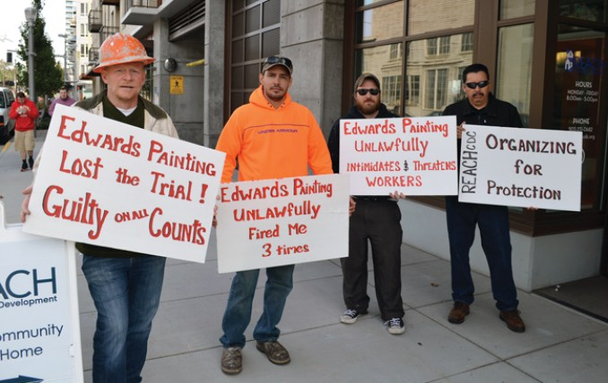 On Oct. 13, union painters hold signs outside the South Waterfront headquarters of Reach CDC, a non-profit developer of low-income housing. Reach hired general contractor R&H, which hired Edwards Painting.