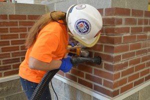 Bricklayers Local 1 apprentice Krista Kiser grinds a mortar joint with a vacuum attached.